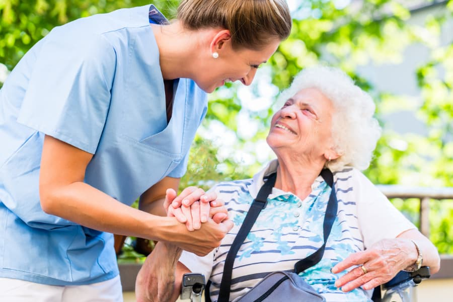 caregiver holding hand of senior woman