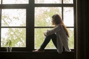 girl sitting on window bench looking out window
