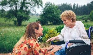 young woman talking with elderly woman in wheelchair