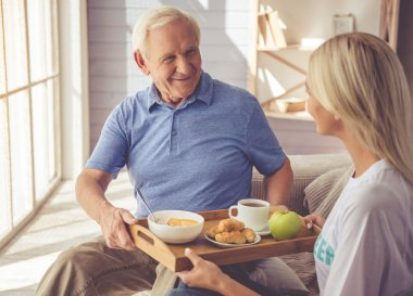 elderly man receiving a breakfast tray from young woman