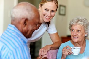 smiling woman caregiver with elderly couple who are having coffee at table