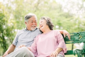 senior couple sitting on a bench laughing