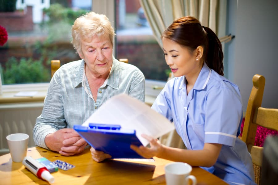 young home health nurse sitting at a table with an elderly woman talking
